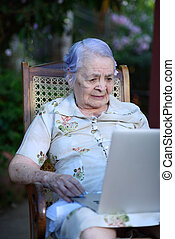 Grandma with laptop - Grandma using and talking on a laptop