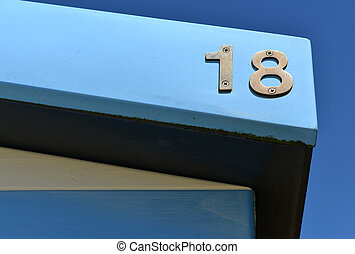 Number on colourful beach ht with blue sky