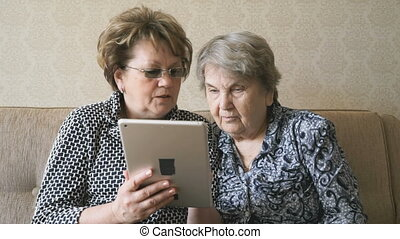 The old woman and her friend looking at pictures