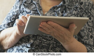 Old woman looks at photos using a digital tablet