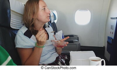 Girl eating cake in airplane - Girl eating cake while flying...