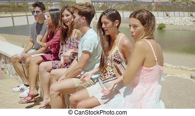 Six teenage friends in shorts socializing at beach - Group...