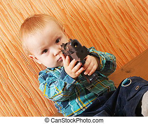 boy plays with gun - Little boy plays with gun in interior