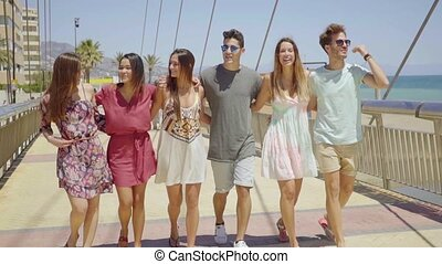 Group of trendy young friends walking arm in arm along a...