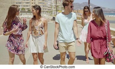 Group of trendy young tourists out sightseeing walking along...