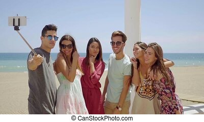Group of young friends on vacation taking a selfie as they...