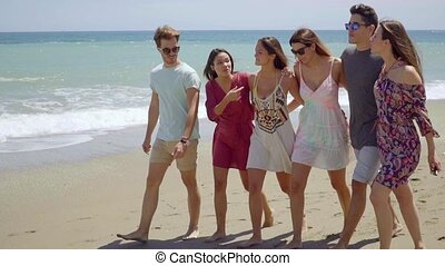 Happy group of young students walking on a beach - Happy...
