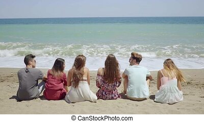 Six young people sitting overlooking the ocean - Six young...