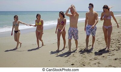 Group of multiracial young friends on a beach - Group of...