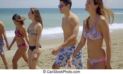 Group of diverse young friends walking on a beach - Group of...