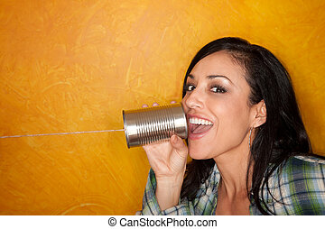 Hispanic woman with tin can telephone - Attractive Hispanic...