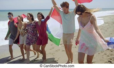 Group of Friends with Flags Walking on Sunny Beach - Group...