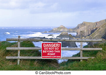 Dangerous clifftop - Dangerous cliff edge with warning sign.