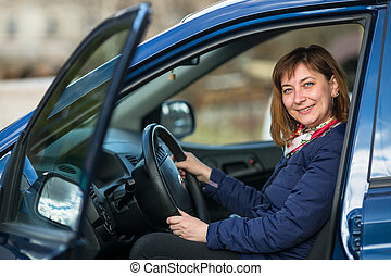 A young woman in his new car.