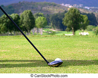 Tee off - Golf club and ball on the tee with the fairway in...