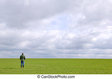 Man in a field - A man standing in a green field under a...
