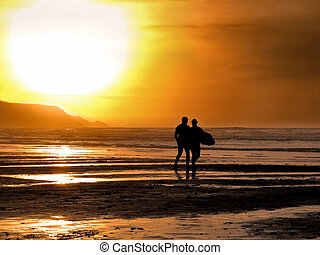 Sunset surfers - Silhouette of a male and female surfer...