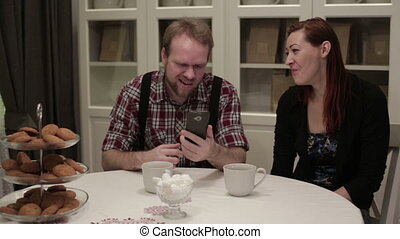 Two people sitting at the table doing selfie