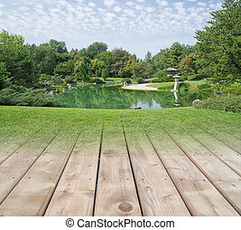 Wooden deck transitioning into beautiful green park with a lake background