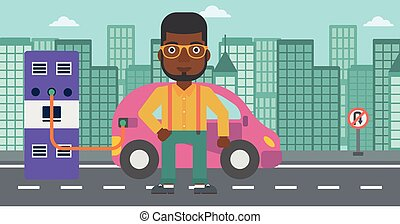 Charging of electric car - An african-american man charging...