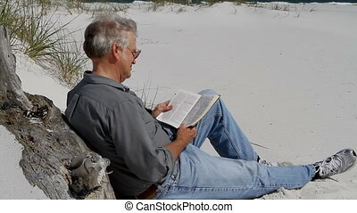 Man Reading Bible At Beach - Mature man sits leaning against...