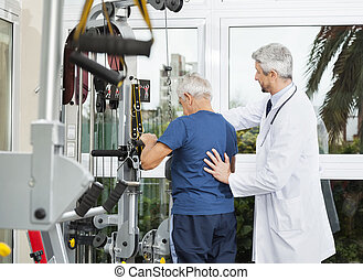 Doctor Assisting Senior Man To Use Exercise Machine - Mature...