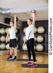 Young Friends Lifting Kettlebells In Gym - Full length of...