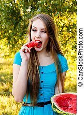 Beautiful blonde girl eating a watermelon outdoors -...