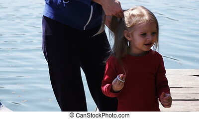 Mother girl braids hair on nature - On river bank Mom girl...