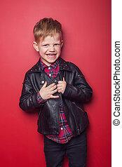Fashion little boy wearing a leather jacket. Studio portrait...