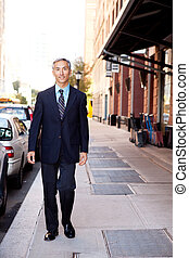 Business Man - An asian looking business man walking in a...