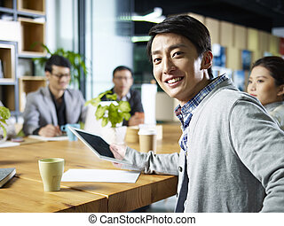 young asian businessman looking at camera - young confident...