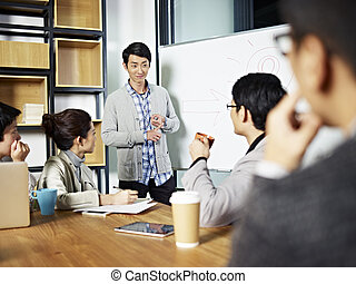 young asian businessman facilitating a discussion - young...