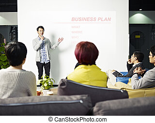 young asian man presenting business plan - young asian...