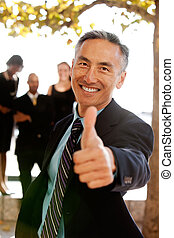 Thumbs Up - An asian looking business man with thumbs up -...
