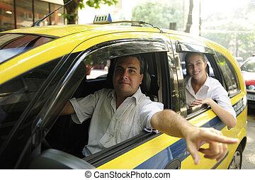 taxi driver showing passenger a landmark while driving