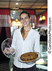 small business: proud female owner of a cafe showing  a cake