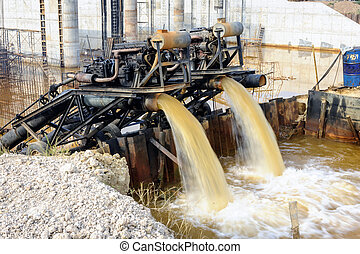 Water pumps are pumping at the dam construction site.