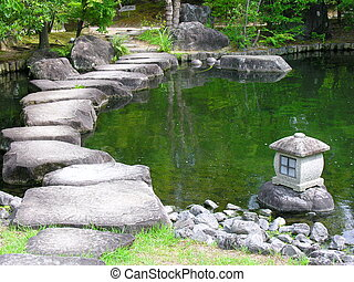 Japan zen path in a garden, pond surrounded