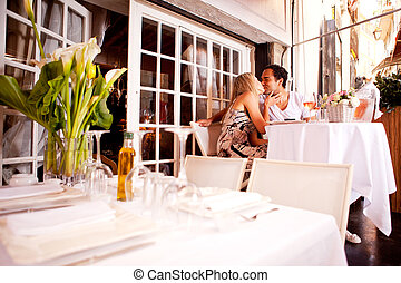 Romantic Couple in Restaurant - A romatic couple kissing in...