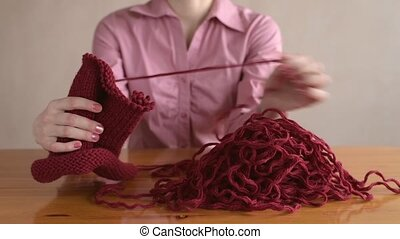 Woman in pink unravelling the knitting - Woman in pink...