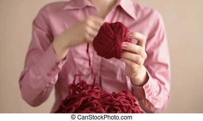 Woman in pink clewing the yarn up - Woman in pink clewing...