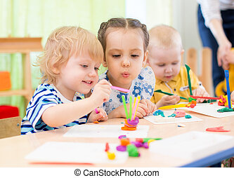 happy kids doing arts and crafts in day care centre - happy...