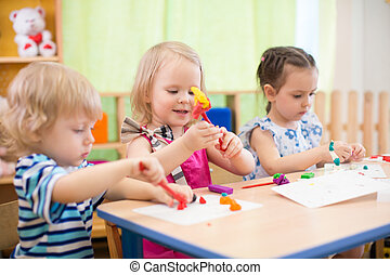 kids group making arts and crafts in kindergarten with...