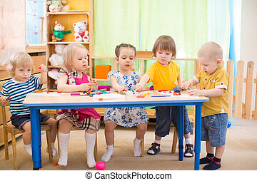 kids group learning arts and crafts in kindergarten playroom...