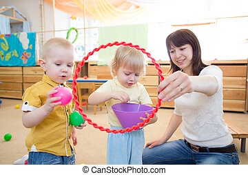 Happy children playing with ball and ring in kindergarten