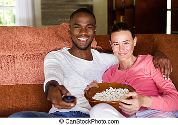 Mixed race couple watching a movie at home