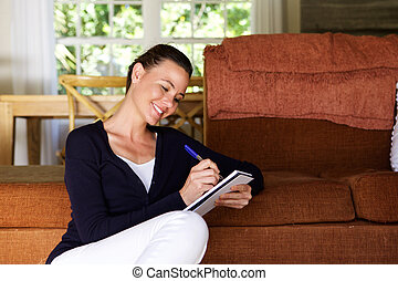 Relaxed woman writing in notebook at home - Portrait of...