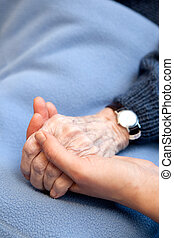 Old Hands - An old handing holding a young hand. Shallow...