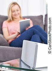 Woman Streams Music From Digital Tablet To Wireless Speaker